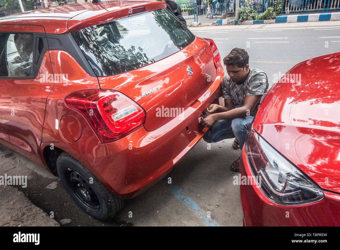 Kolkata, India. 14th May, 2019. An Indian worker sets number plate to a new car in?Kolkata, India, May 14, 2019. India's automobile sector continued its bumpy ride for the fifth consecutive month in April with 20 percent drop in car sales and 16 percent drop in two-wheeler sales, compared with the same period last year. The drastic drop in sales was attributed to several factors including liquidity squeeze in the market, rising fuel cost, interest rates and insurance costs that has dampened consumer sentiment. Credit: Tumpa Mondal/Xinhua/Alamy Live News Stock Photo