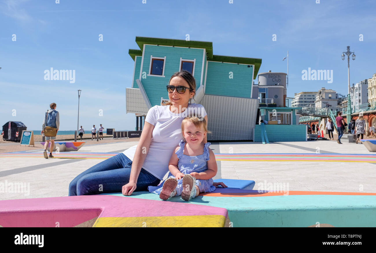 Brighton, UK. 14th May, 2019. A young mum and her 2 year old daughter enjoy themselves on Brighton seafront on a hot sunny day with warmer weather forecast for the next couple of days throughout Britain . Credit: Simon Dack/Alamy Live News - Stock Image