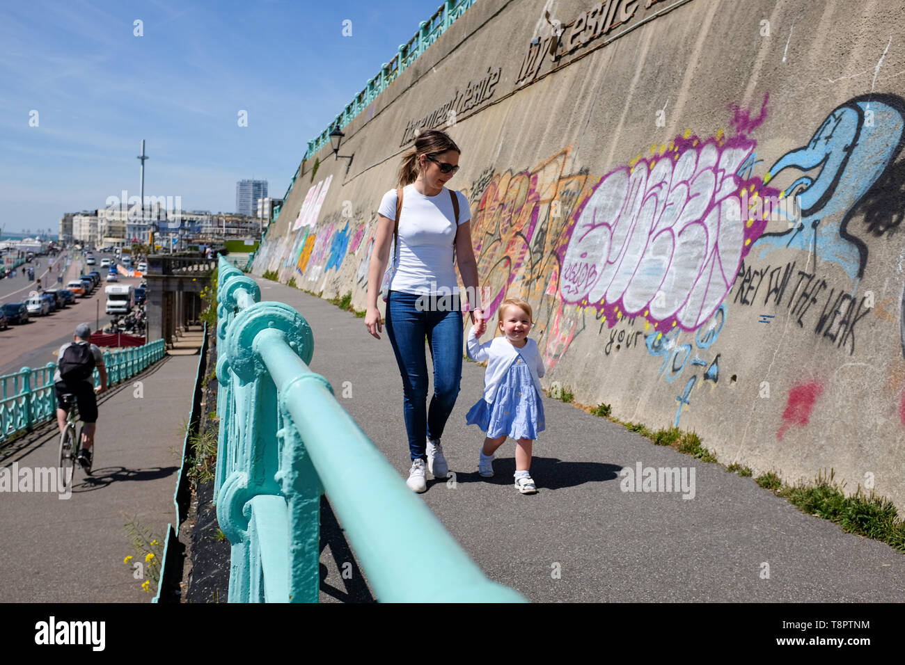 Brighton, UK. 14th May, 2019. A young mum and her 2 year daughter enjoy a walk along Brighton seafront on a hot sunny day with warmer weather forecast for the next couple of days throughout Britain . Credit: Simon Dack/Alamy Live News - Stock Image