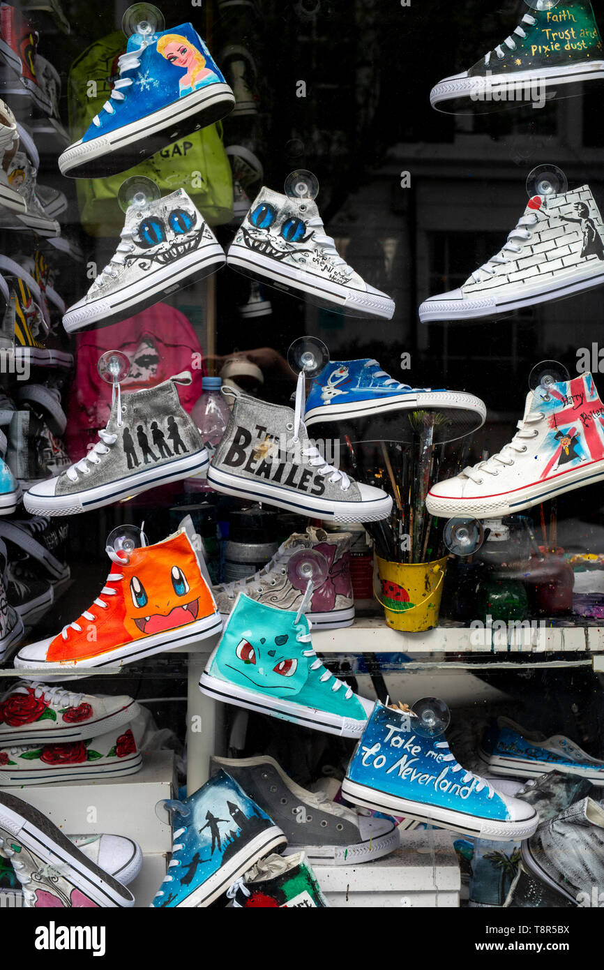 Hand painted Converse trainers in a shop window. Pembridge road, Notting Hill, London - Stock Image