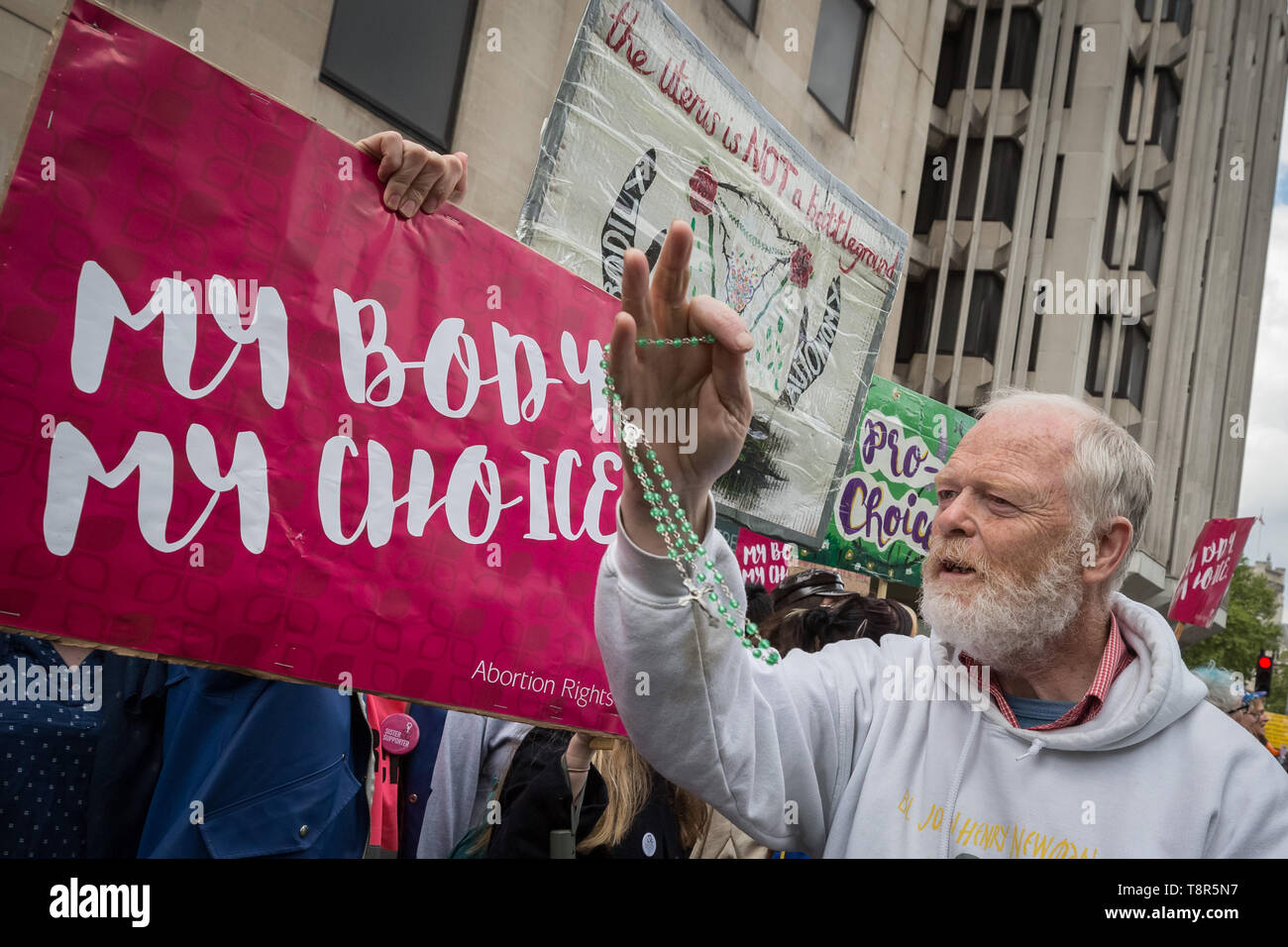 An anti-abortion Christian waves his holy rosaries at women's rights pro-choice supporters as the groups clash during March for Life UK protest. - Stock Image