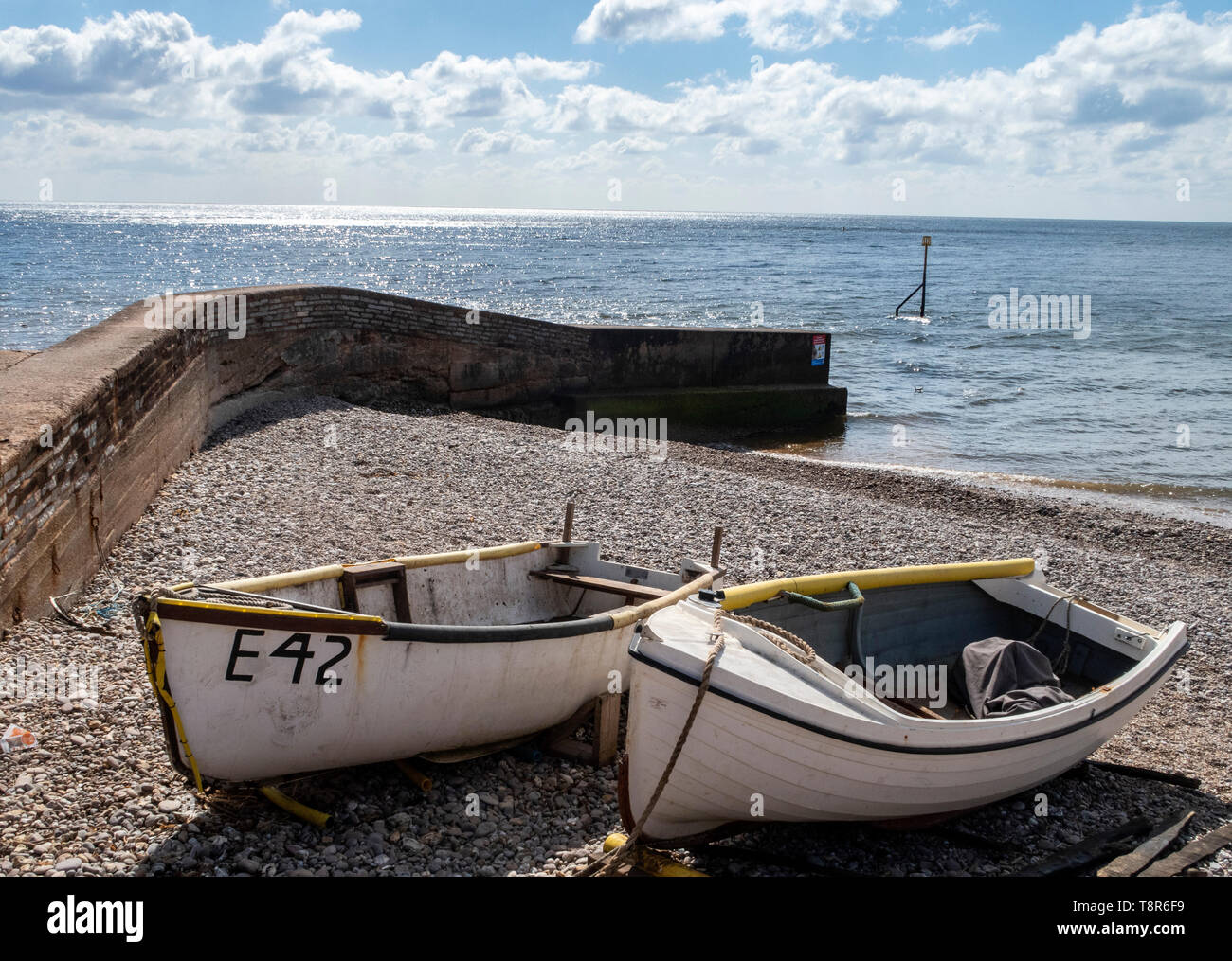 Fishing boats pulled up onto the shore beside a sea wall at Sidmouth, Devon, UK Stock Photo