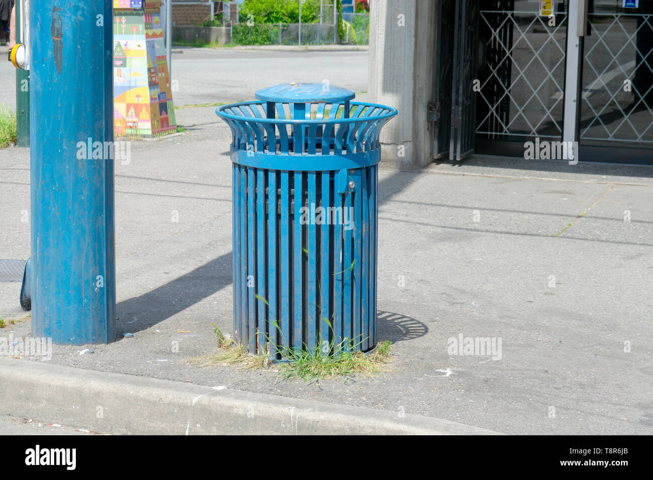 A blue garbage receptacle and matching pole on a city street in Vancouver, British Columbia, Canada. - Stock Image