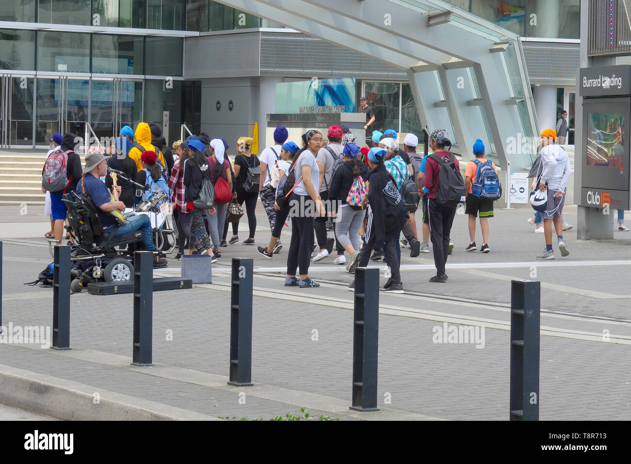 A group of young people gathered at Vancouver Convention Centre.  A street musician entertains. - Stock Image