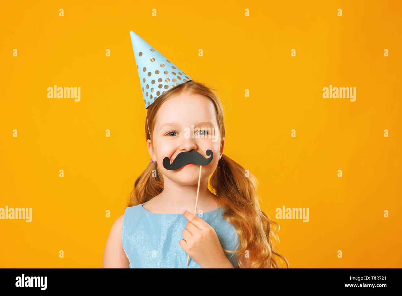 Happy father's day. Funny little girl with fake mustache on yellow background. Family concept. - Stock Image