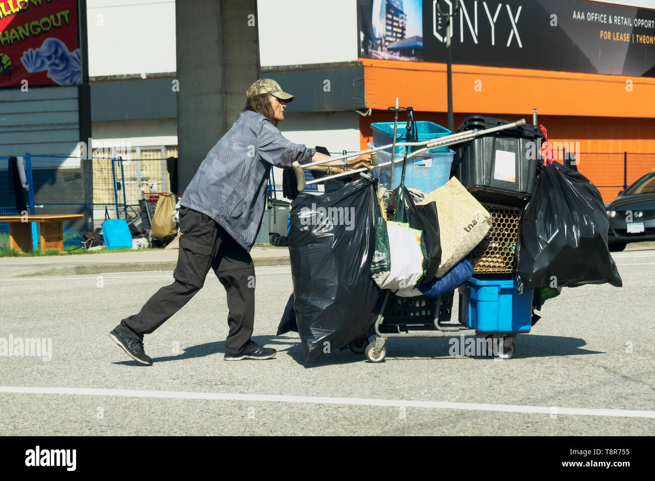 A homeless man walking across an intersection pushing a shopping cart loaded with his worldly possessions. - Stock Image