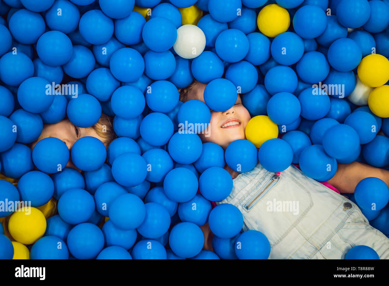 Child playing in ball pit. Colorful toys for kids. Kindergarten or preschool play room. Toddler kid at day care indoor playground. Balls pool for Stock Photo