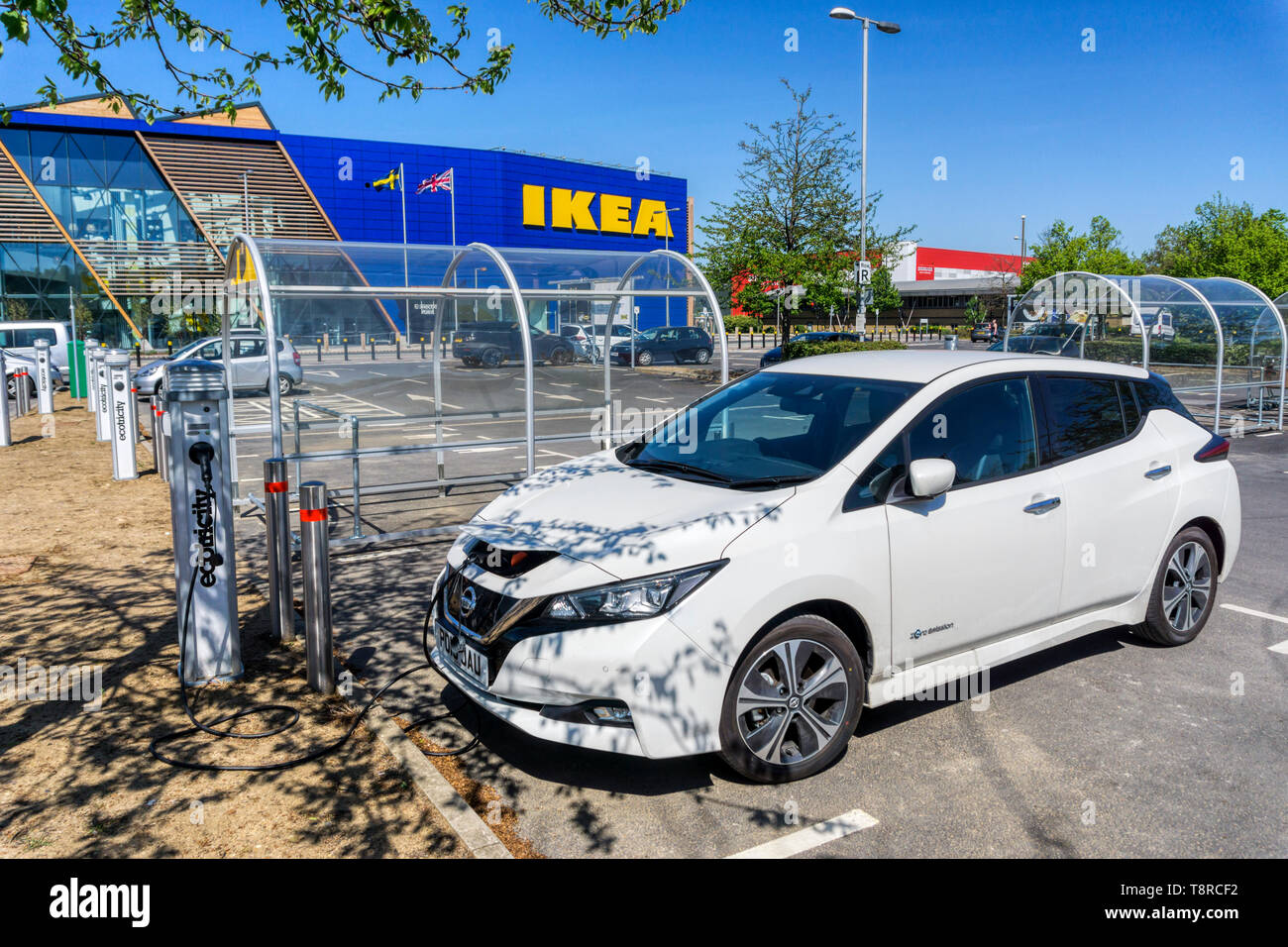 A Nissan LEAF electric car charging at an Ecotricity charging point outside the large IKEA store on the Greenwich Peninsula. - Stock Image