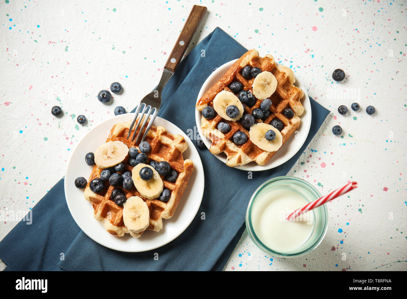 Delicious waffles with banana slices, blueberries and glass of milk on light table - Stock Image