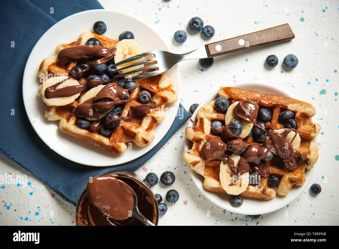 Delicious waffles with banana slices, blueberries and chocolate sauce on light table - Stock Image