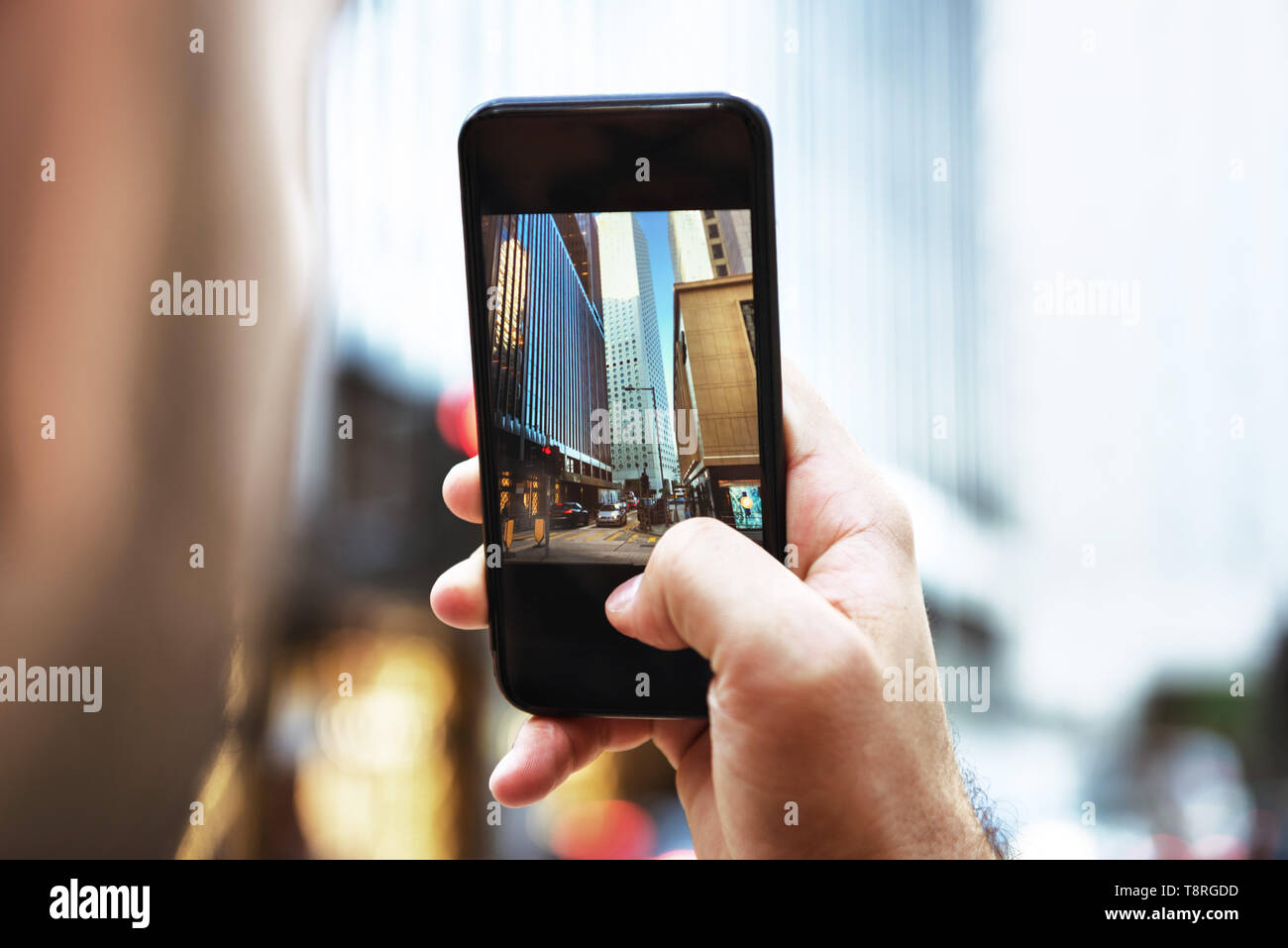 Man takes mobile photo of big city Stock Photo