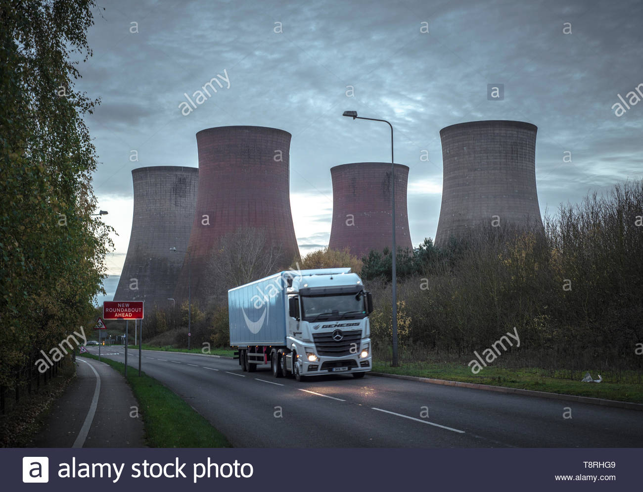 Busy road at dusk with cooling towers of Rugeley power station, recently closed, in the background.  Rugeley, Staffordshire, UK - Stock Image