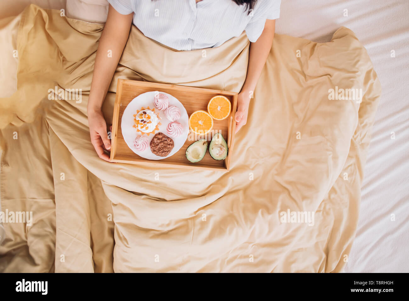 Cropped photo of woman sitting in bed with cream color blanket and having breakfast. Top view. Healthy and tasty breakfast, meal, food, morning, home  - Stock Image