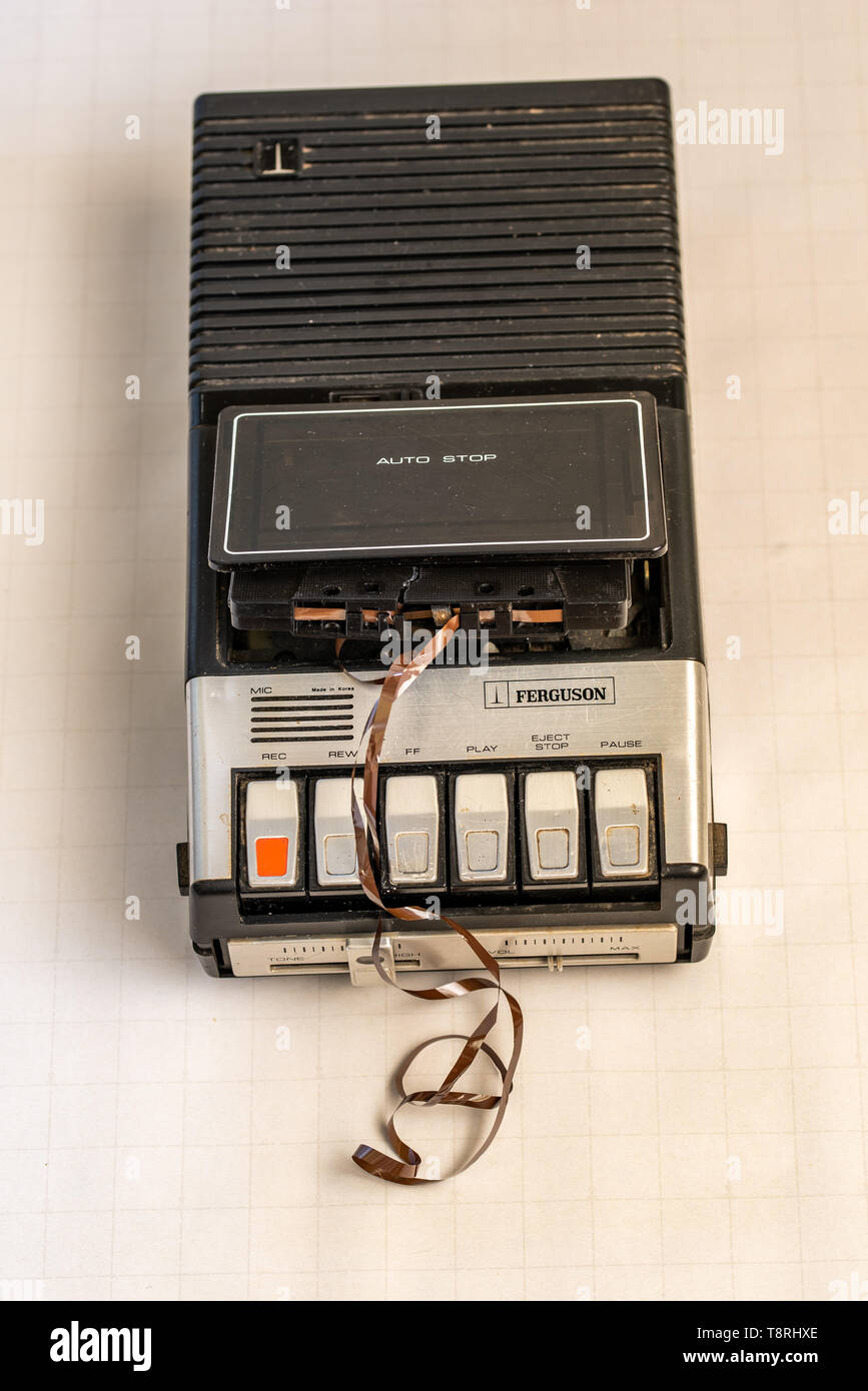A retro cassette player with a broken cassette tape. - Stock Image