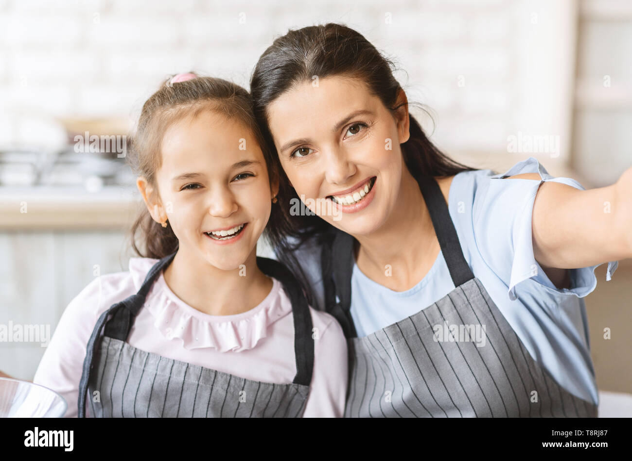 Cute Little Girl And Her Mom In Aprons Making Selfie - Stock Image