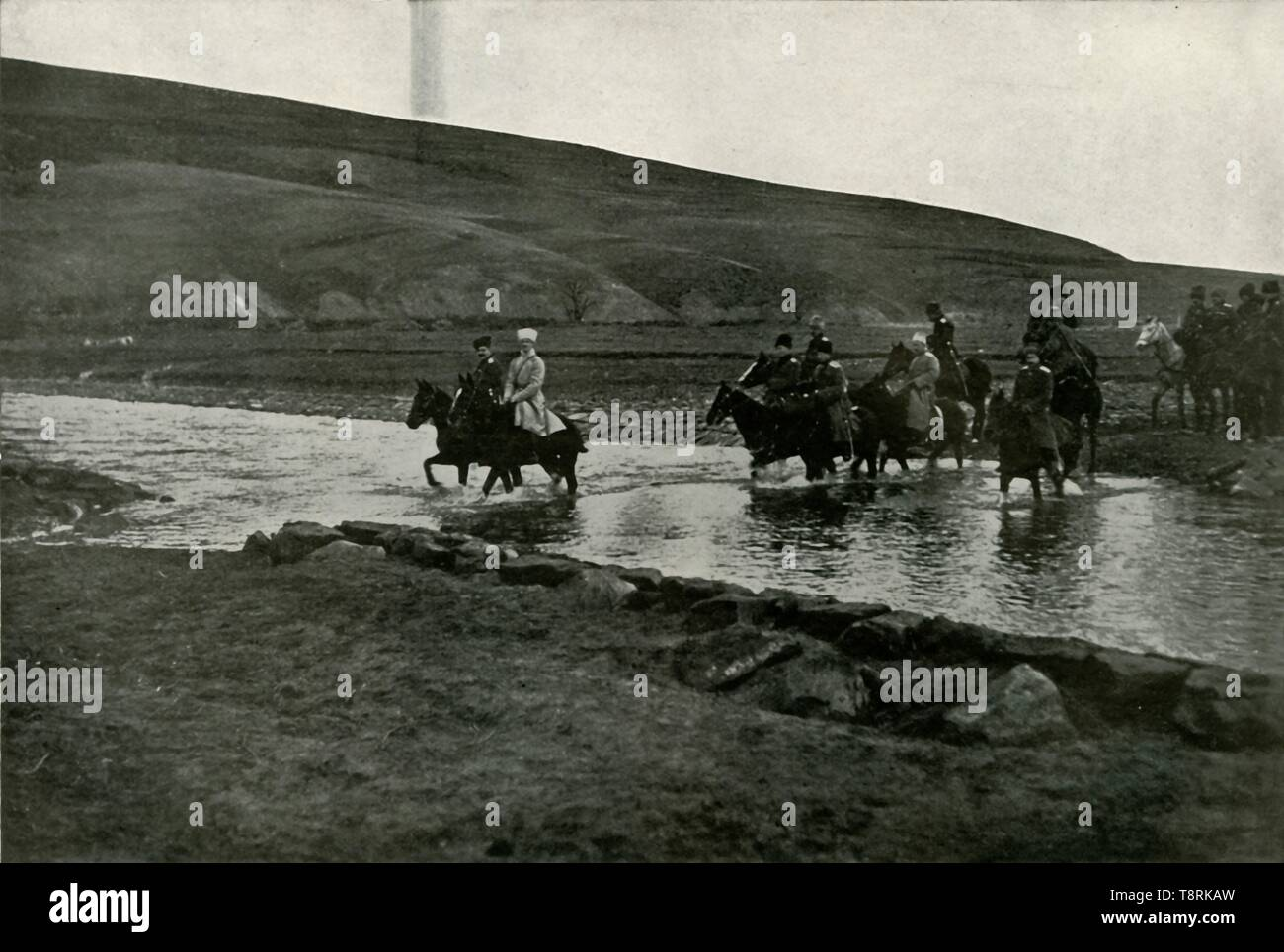 """'The Grand Duke Michael and his Staff', (1919). Scene from the First World War, 1914-1919: 'The Grand Duke [Michael Alexandrovich of Russia 1878-1918], commanding the Caucasian Native Division, is shown crossing a small tributary of the San River, which flows through the low foothills of the Carpathians, which here somewhat resemble the South Downs in appearance.' From """"The History of the Great European War: its causes and effects"""", Vol. IV, by W. Stanley Macbean Knight. [Caxton Pulishing Company, Limited, London, 1919] - Stock Image"""