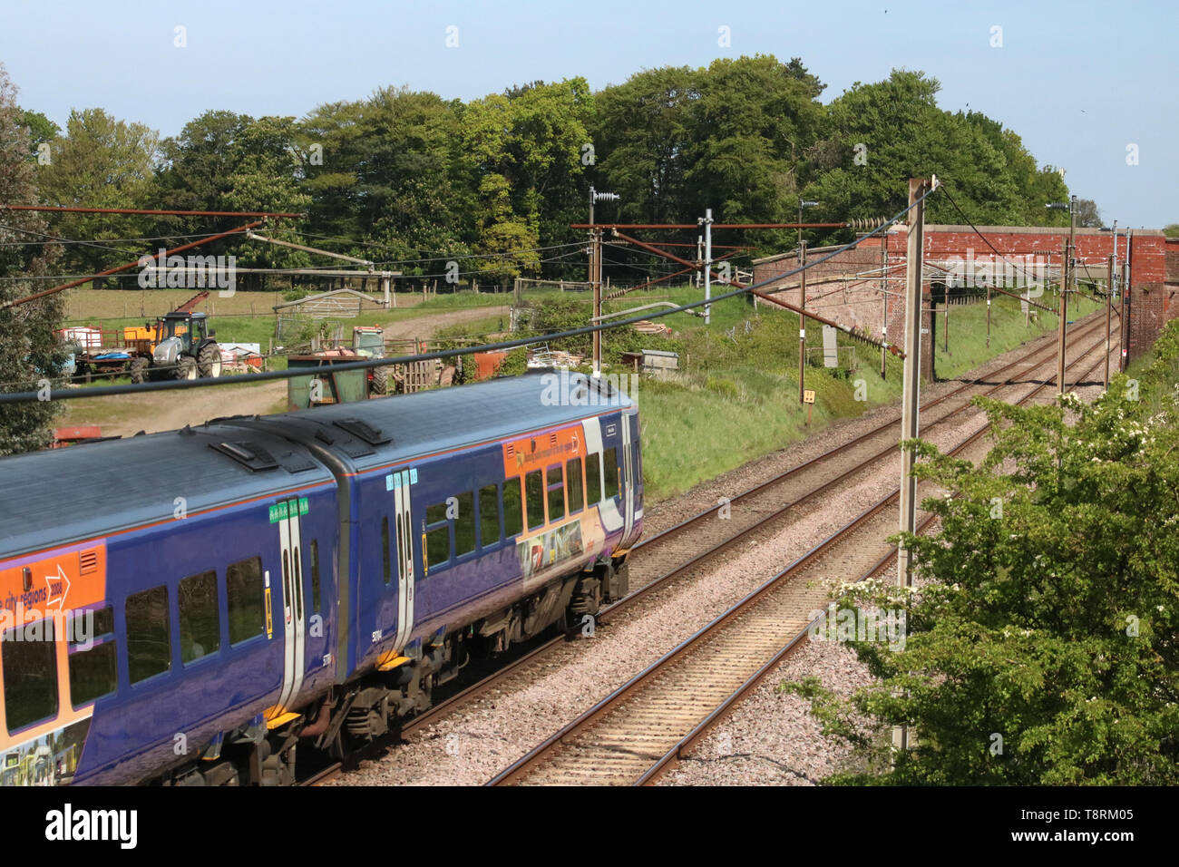 Class 158 two-car express sprinter diesel multiple unit passenger train in Northern livery on WCML near Garstang in Lancashire on 14th May 2019. - Stock Image