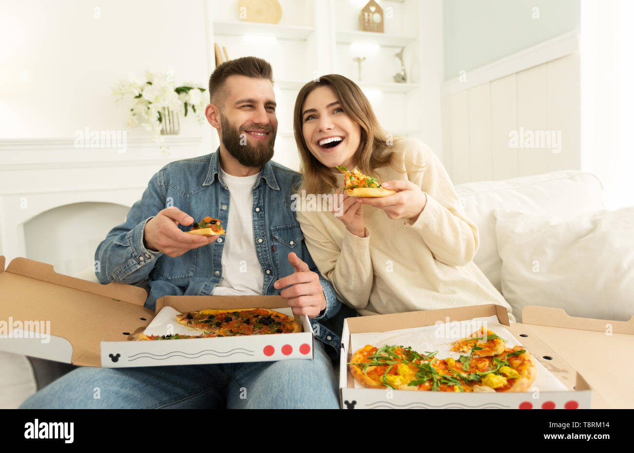Cheerful Couple Eating Pizza In Front Of TV - Stock Image