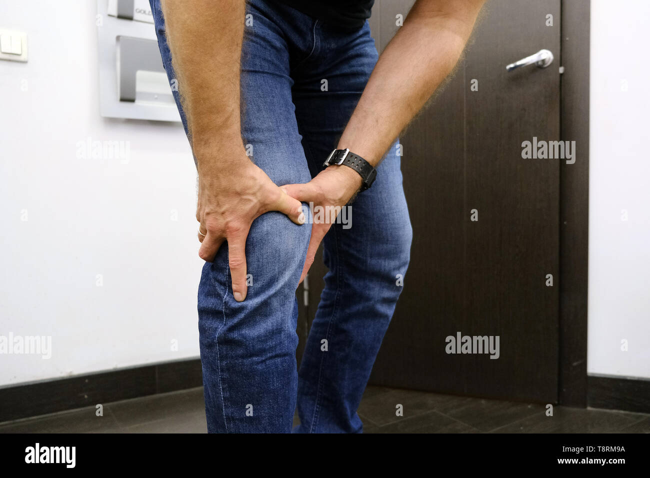 The young man is suffering from knee pain. Sports injury, dislocation, sprain. Inflamed knee ligaments. - Stock Image