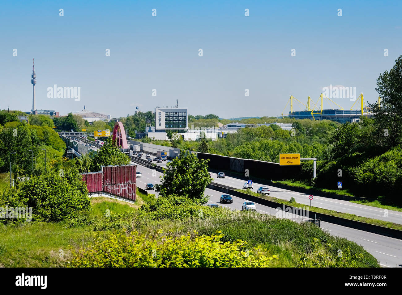 Skyline of Dortmund, with motorway A40 (Ruhrschnellweg) in Dortmund as federal highway No. 1 with football arena Westfalenstadion (Signal Iduna Park), Westfalenhalle and TV tower Florianturm in Westfalenpark. - Stock Image