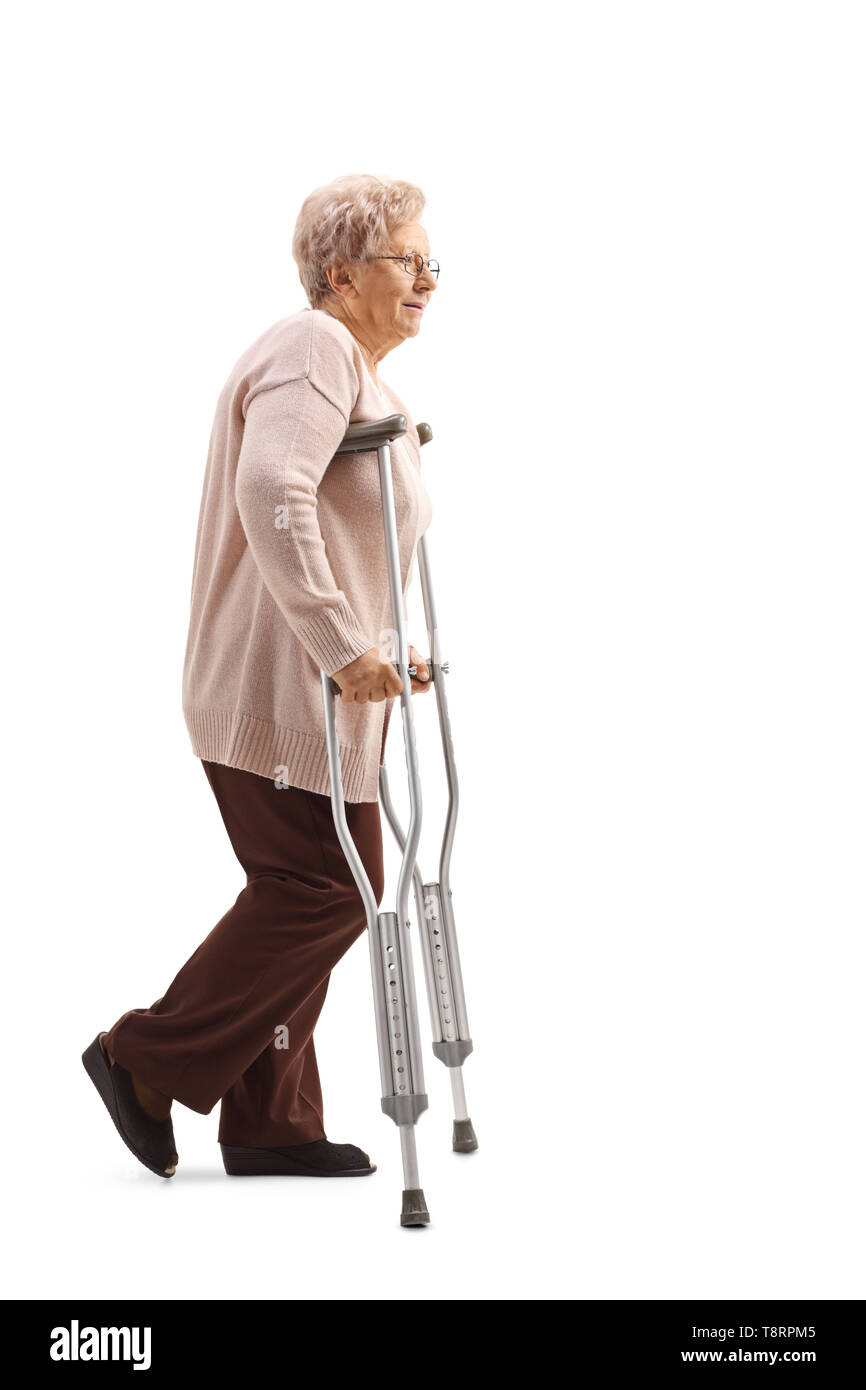 Full length profile shot of a senior woman walking with crutches isolated on white background - Stock Image