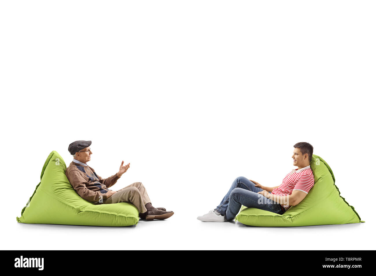 Full length profile shot of a young and elderly man sitting on bean bags and talking isolated on white background - Stock Image