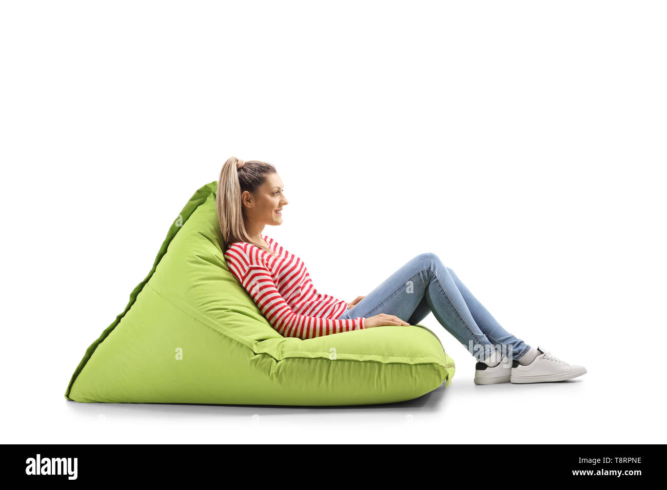 Full length profile shot of a young blond casual woman sitting on a green bean bag isolated on white background - Stock Image