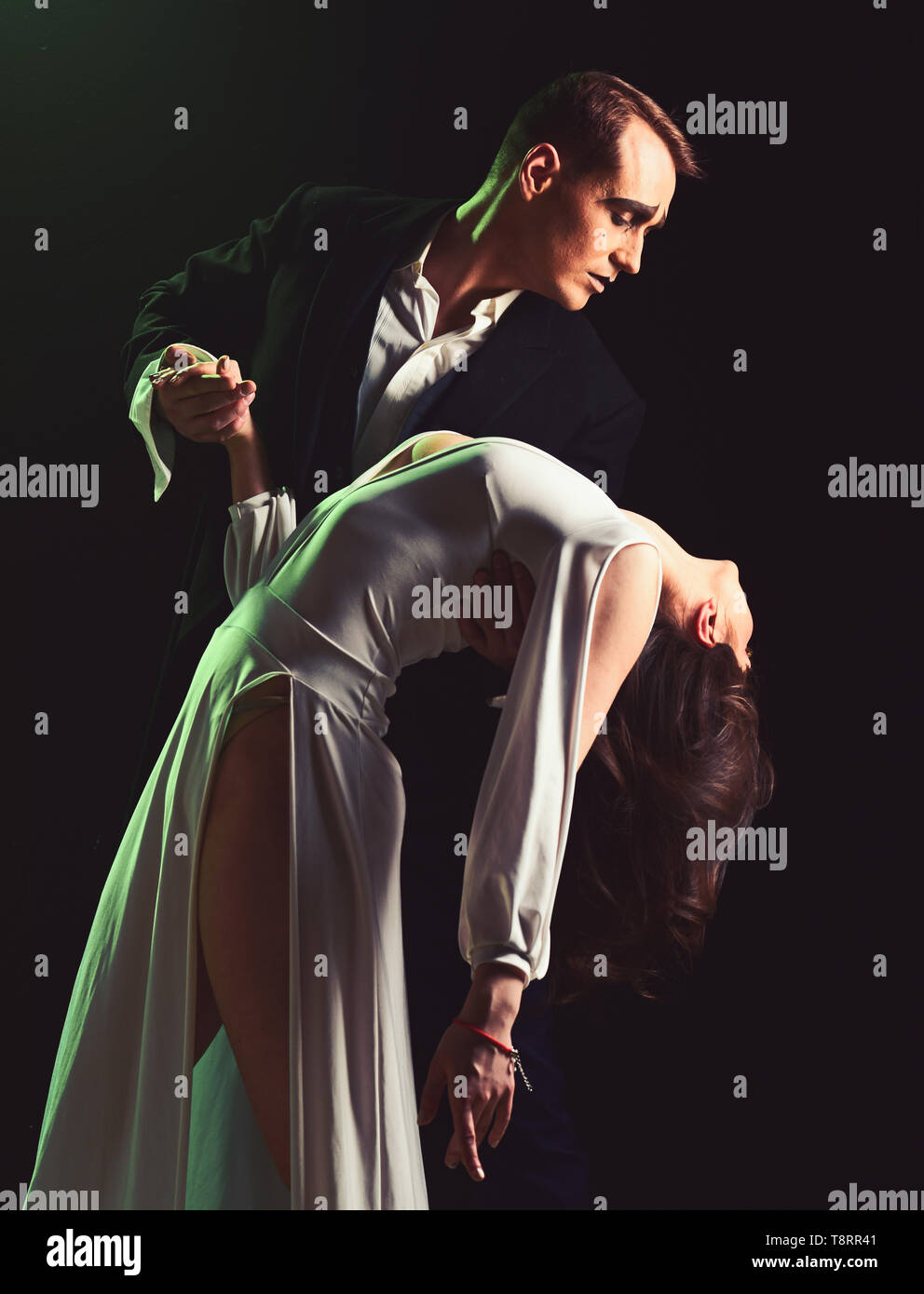 Too many emotions. Mime man and woman act in romantic scene. Couple of mime artists perform romance on stage. Couple in love with mime makeup. Theatre - Stock Image