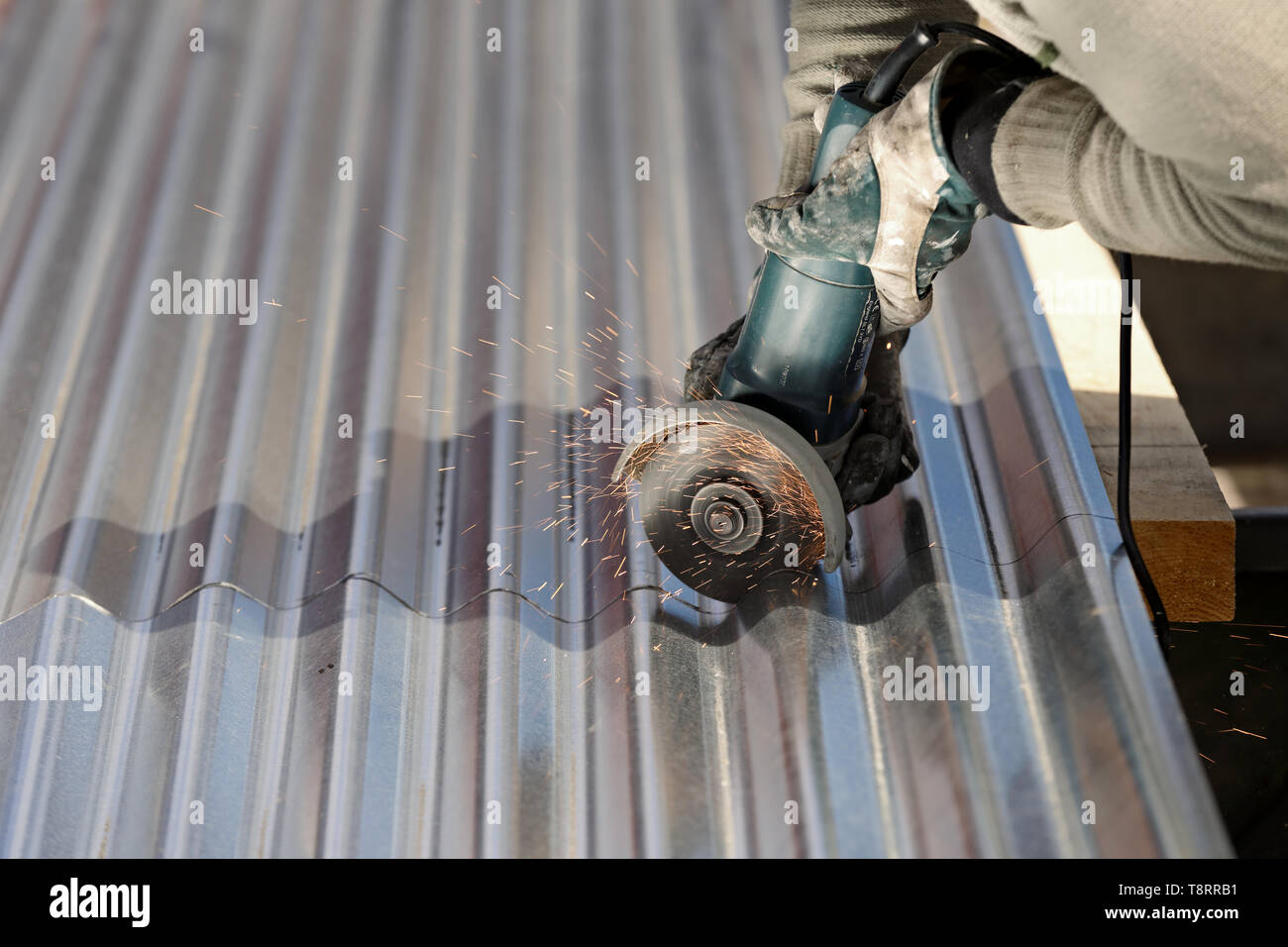 A man cutting steel plate with an angle grinder - Stock Image