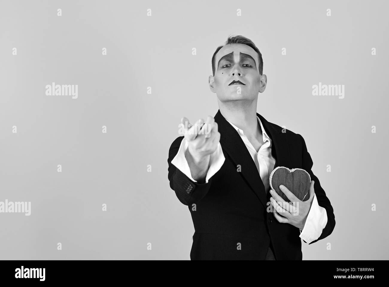 Seems as a real love. Love confession on valentines day. Mime man hold red heart for valentines day. Mime actor with love symbol. Theatre actor - Stock Image