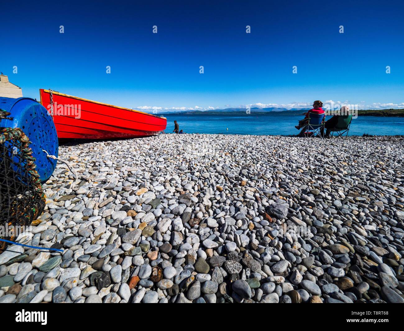 Staycation - British Beach Holidays - Anglesey - shingle beach with red boat - Stock Image