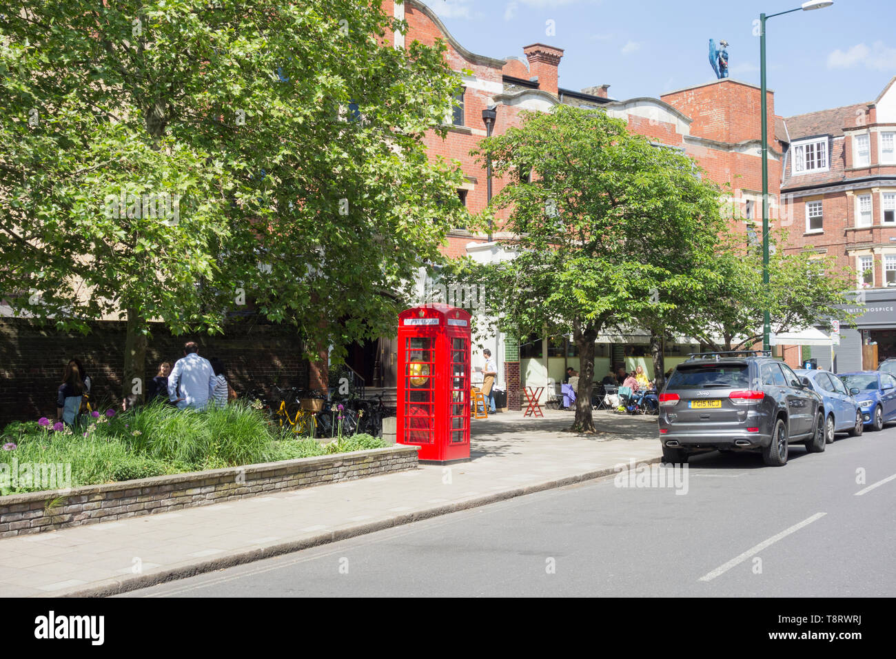 A converted Sir Giles Gilbert Scott K6 phone box, now used to store a defibrillator, in front of the Olympic Cinema, Church, Barnes, London, SW13, UK - Stock Image