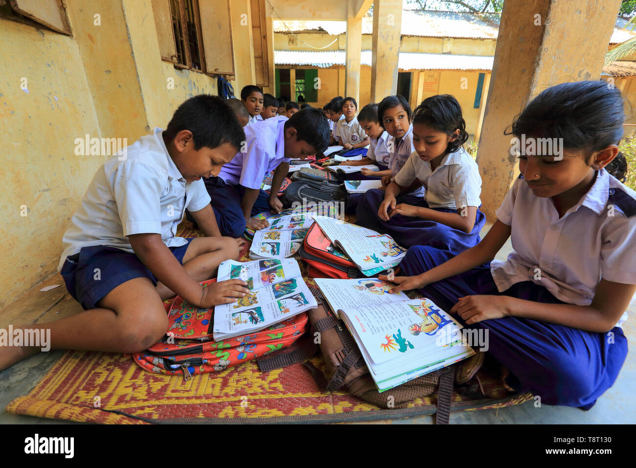 Students of a primary school attend classes on the verandah because of the dilapidated condition of their classrooms. Narsingdi, Bangladesh - Stock Image