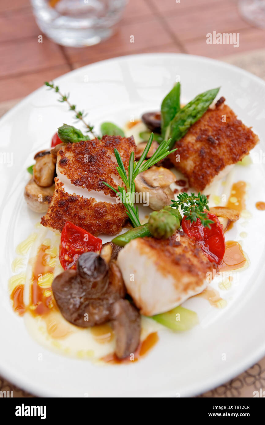 Coalfish fillet with mushrooms and asparagus on plate - Stock Image