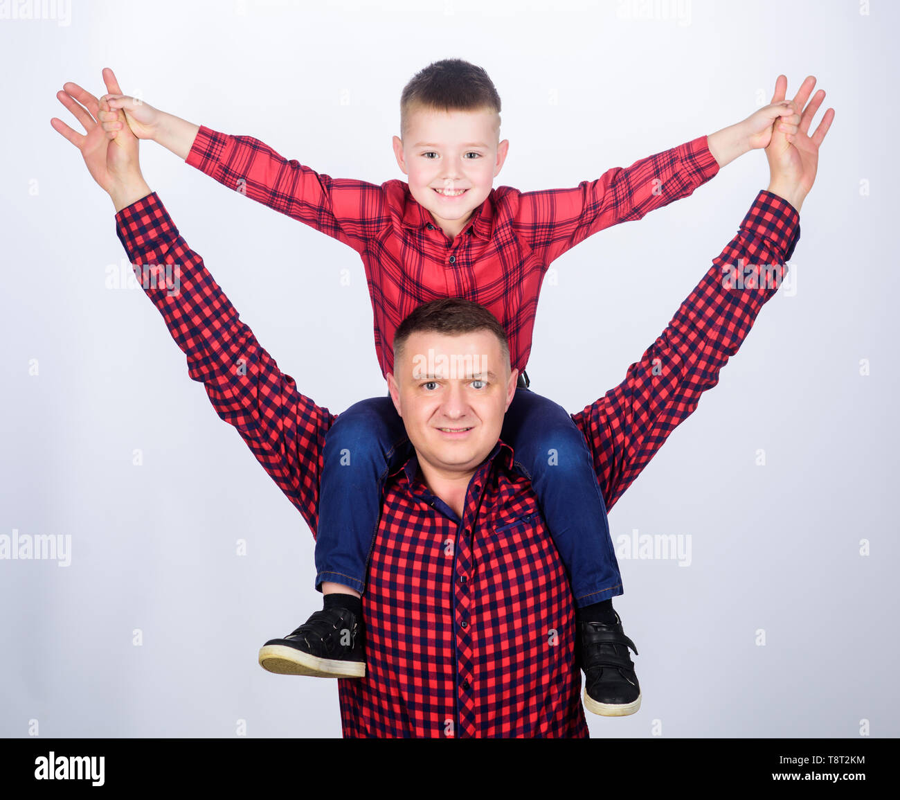 Father little son red shirts family look outfit. Child riding on dads shoulders. Happiness being father of boy. Having fun. Fathers day. Father example of noble human. Family time. Best friends. - Stock Image