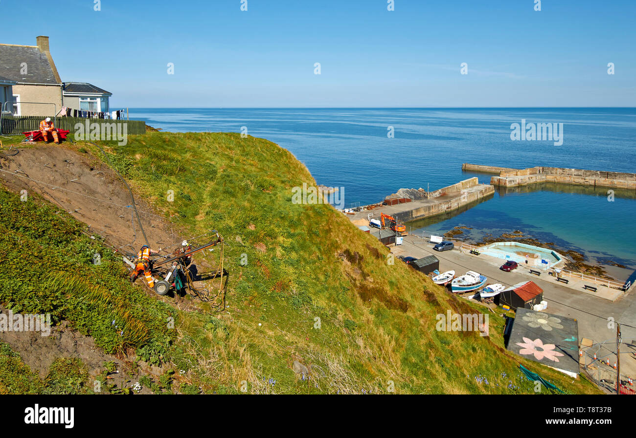 PORTKNOCKIE MORAY SCOTLAND MEN REPAIRING LANDSLIPS BY DRILLING SCREWS INTO CLIFFS IN THE HARBOUR AREA - Stock Image
