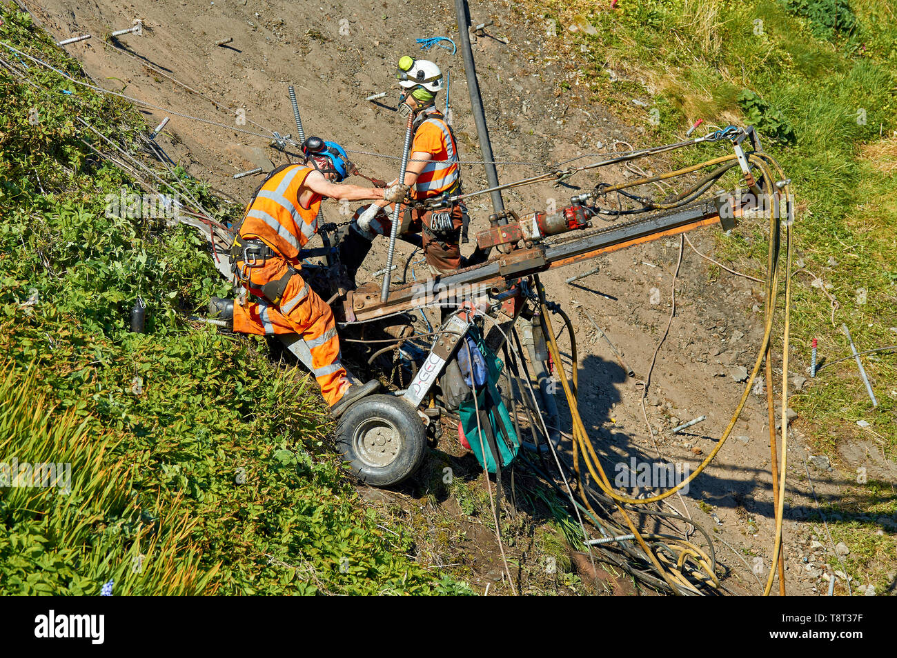 PORTKNOCKIE MORAY SCOTLAND MEN REPAIRING LANDSLIPS ON CLIFFS IN THE HARBOUR AREA - Stock Image