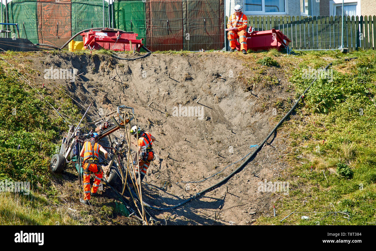 PORTKNOCKIE MORAY SCOTLAND THREE MEN REPAIRING LANDSLIPS BY DRILLING HUGE SCREWS INTO CLIFFS IN THE HARBOUR AREA - Stock Image