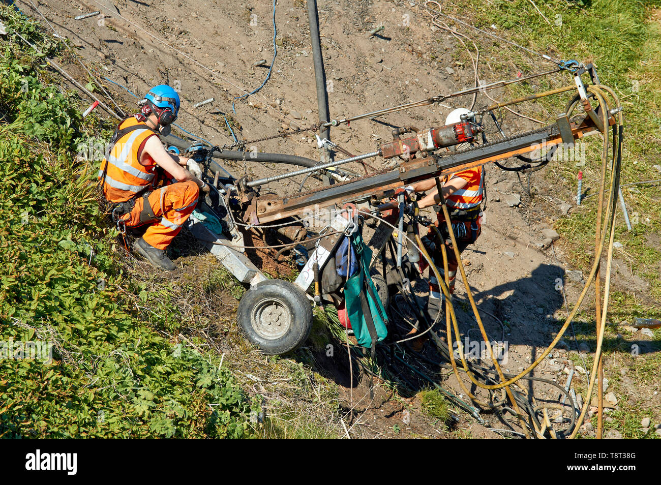 PORTKNOCKIE MORAY SCOTLAND TWO MEN REPAIRING LANDSLIPS BY DRILLING LARGE SCREWS INTO CLIFFS IN THE HARBOUR AREA - Stock Image