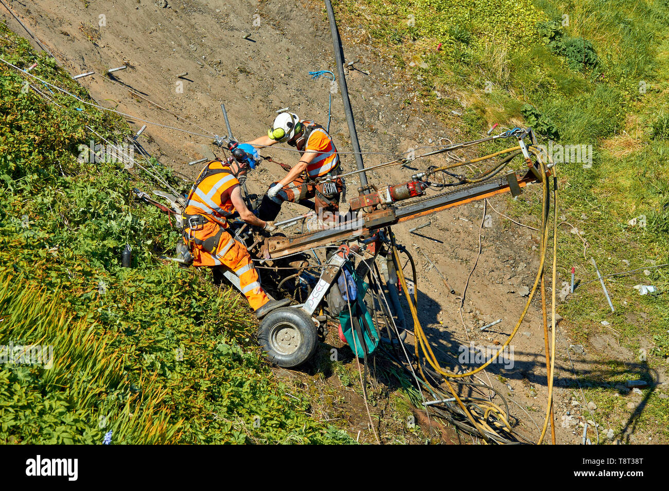 PORTKNOCKIE MORAY SCOTLAND TWO MEN REPAIRING LANDSLIPS BY DRILLING SCREWS INTO CLIFFS IN THE HARBOUR AREA - Stock Image