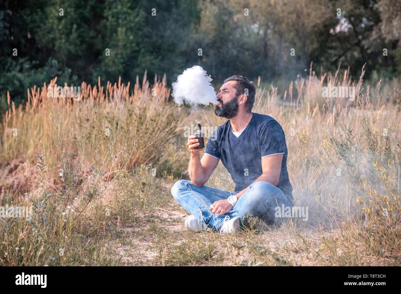 Bearded man smokes electronic cigarette exhales smoke. Alternative to smoking. - Stock Image