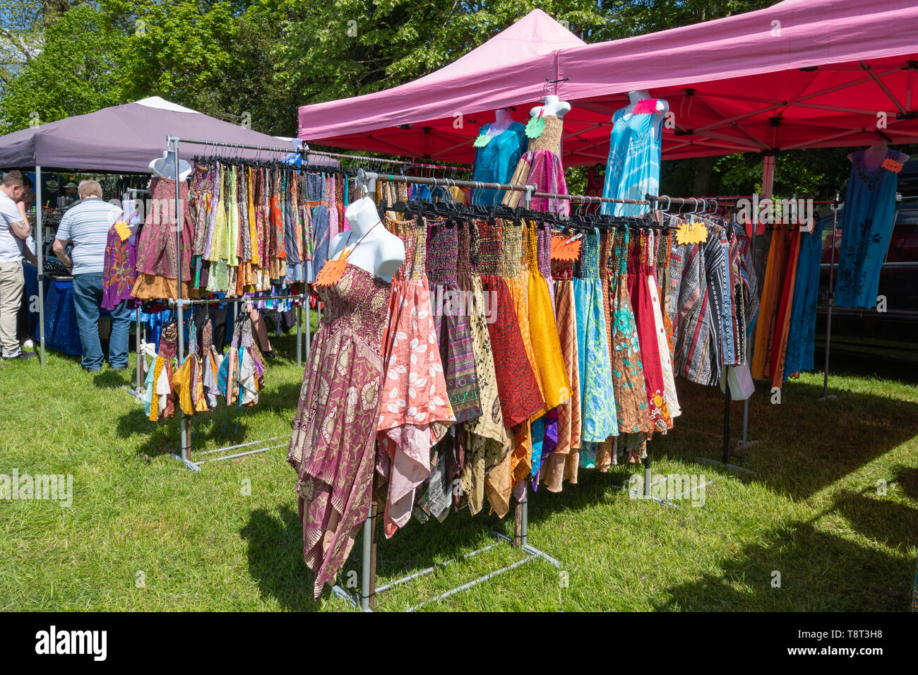 Colourful sun dresses (colourful summer dresses) on sale on a market stall at a show, UK - Stock Image