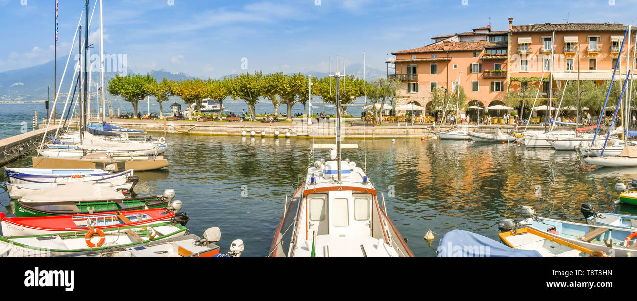 TORRI DEL BENACO, LAKE GARDA, ITALY - SEPTEMBER 2018: Panoramic view of sailing boats in the harbour in the town of Torri del Benaco on Lake Garda. - Stock Image