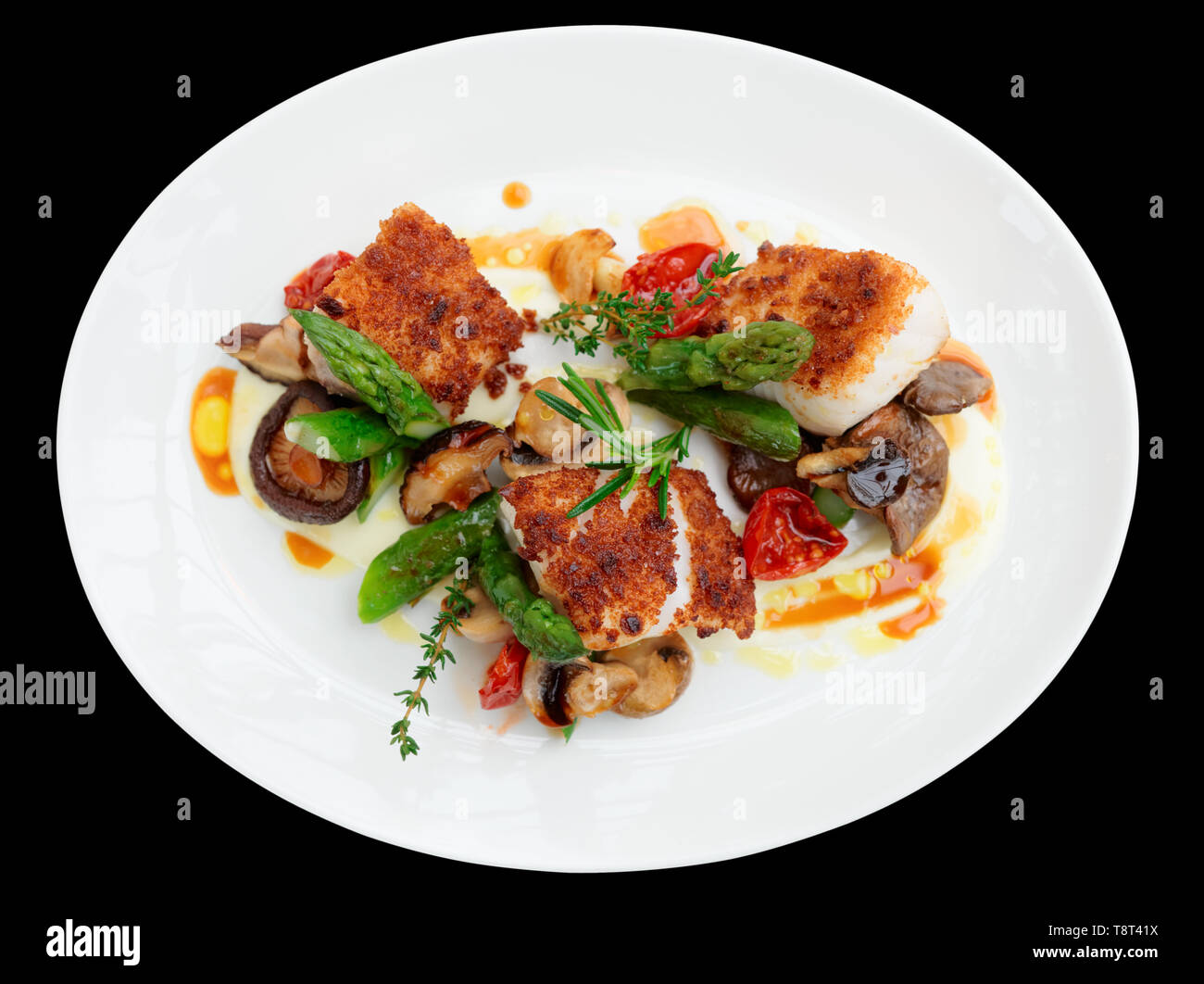 Fish fillet with mushrooms and asparagus isolated on black Stock Photo