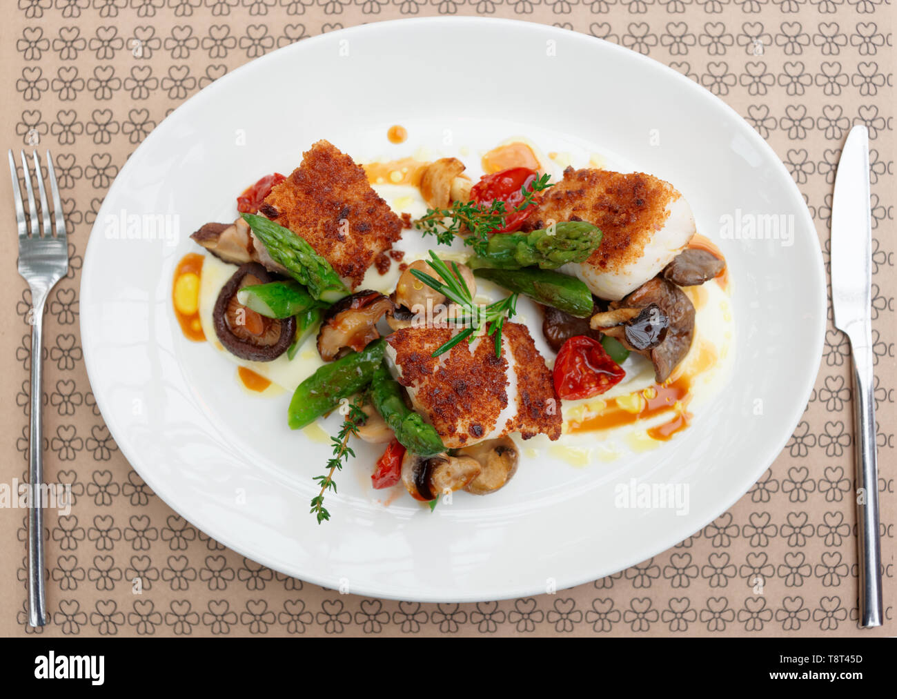 Fish fillet with mushrooms and asparagus on restaurant table - Stock Image