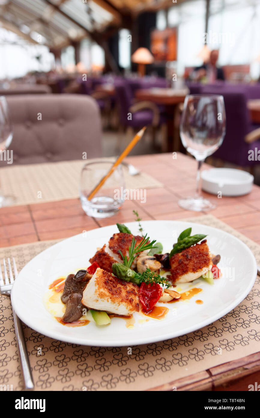 Fish fillet with mushrooms and asparagus on restaurant table Stock Photo