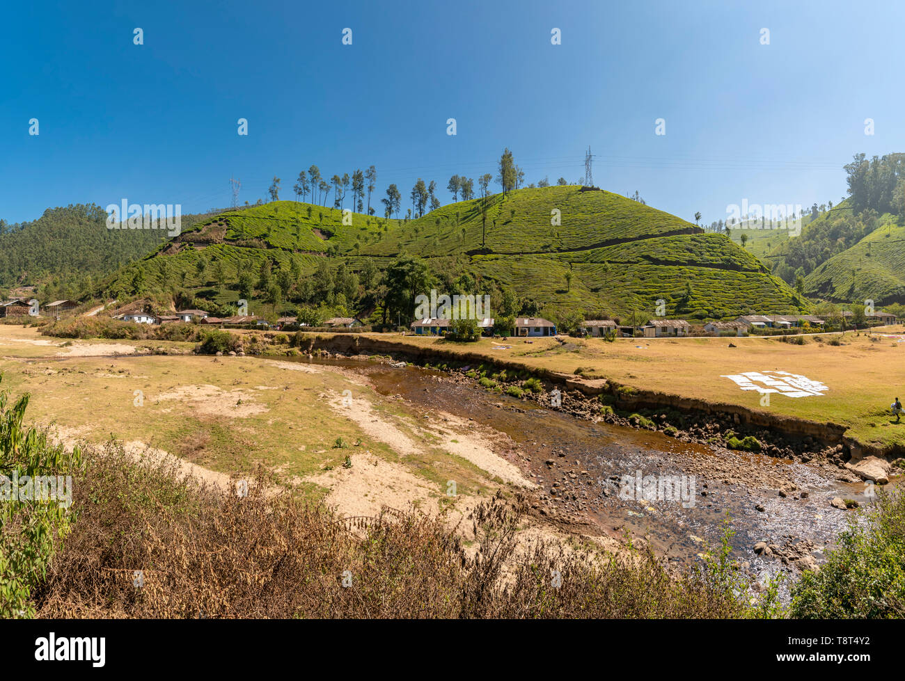 Horizontal panoramic view of a row of hillside cottages infront of a river in Munnar, India. Stock Photo