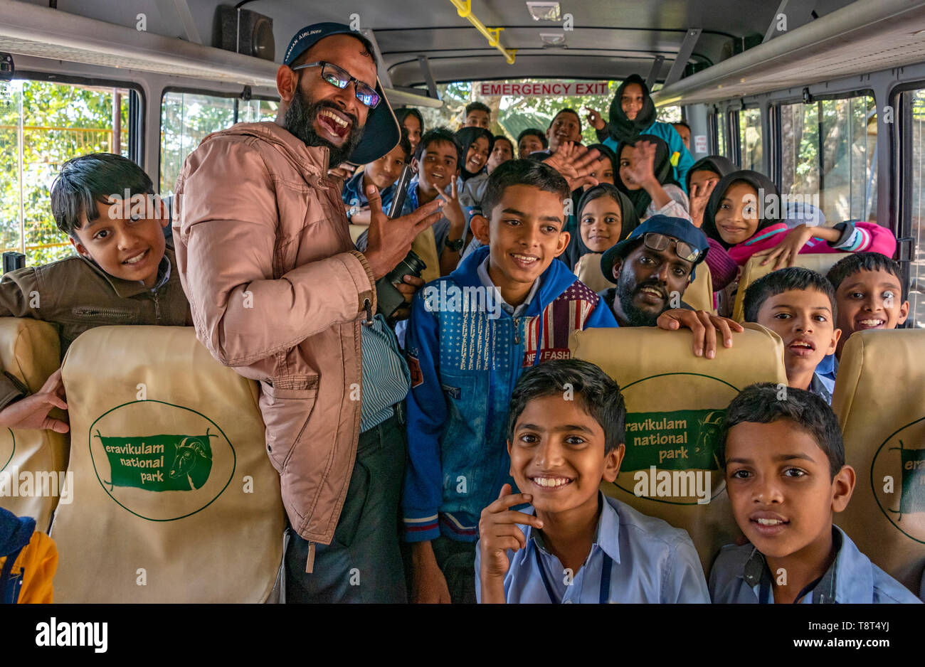 Horizontal view of children and teachers on a school bus in Munnar, India. - Stock Image