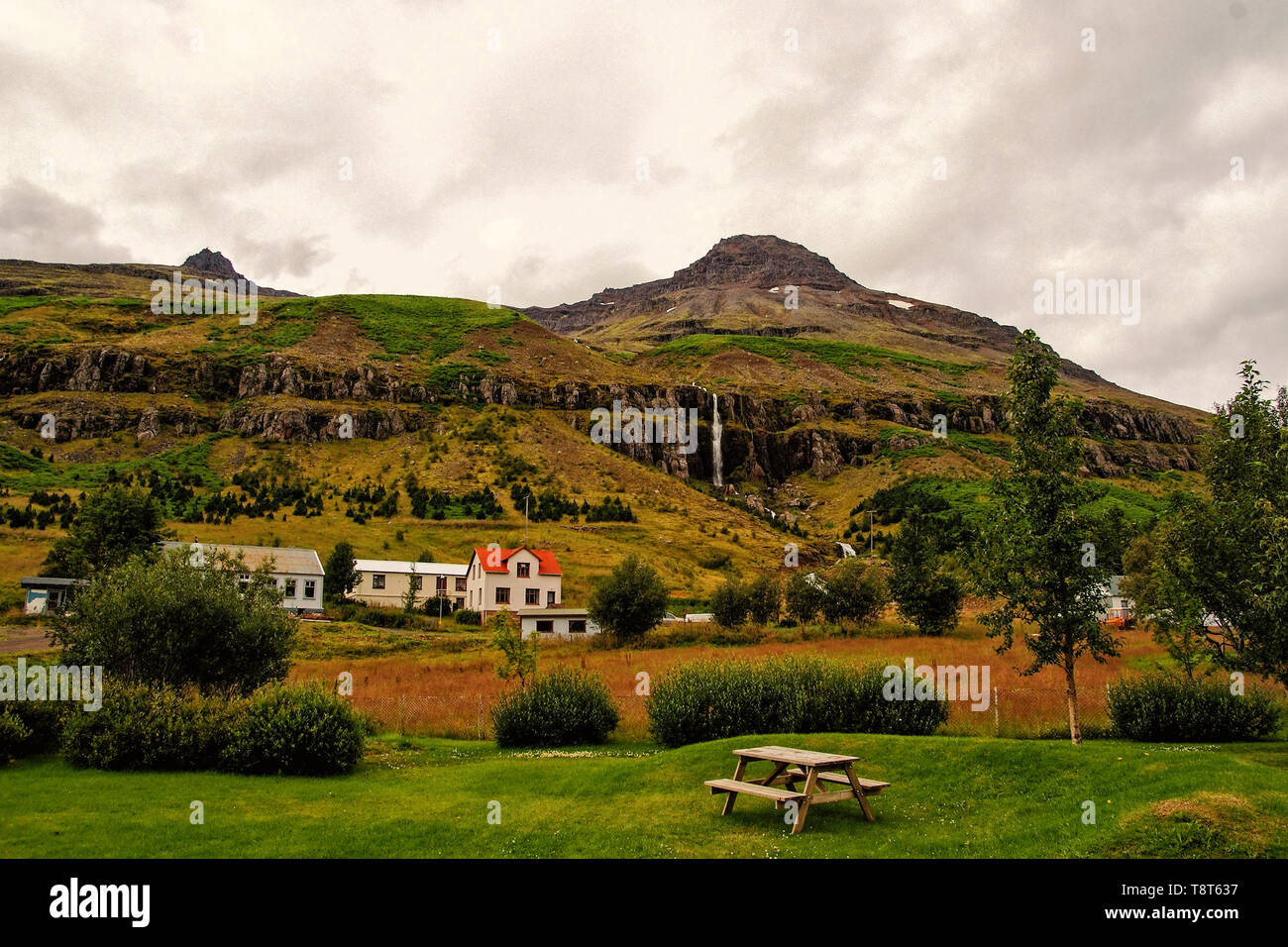 Summer vacation. Travelling and wanderlust. Mountain village on cloudy sky in Sejdisfjordur, Iceland. Country houses on mountain landscape. Living a rural lifestyle - Stock Image