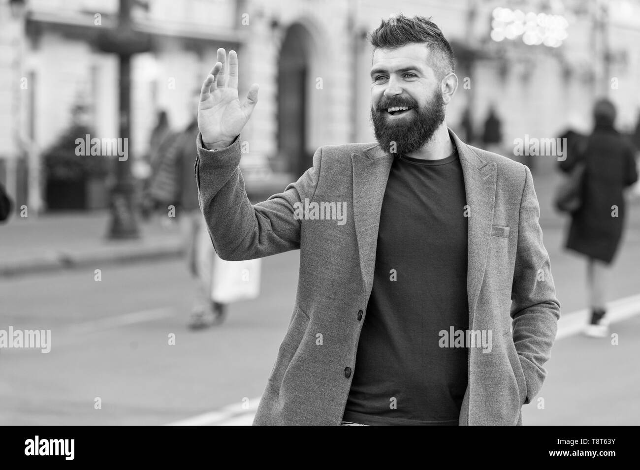 Hipster in casual coat happy to meet friend at urban street. Chance meeting concept. Meet old friend by accident. Man bearded businessman waiting someone in city center. Happy to meet you. - Stock Image